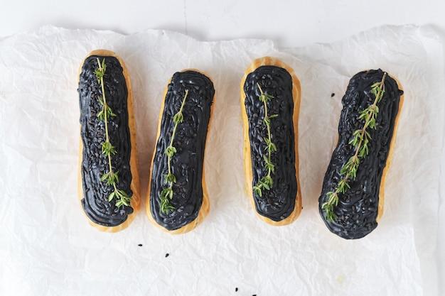 피스타치오 크림과 블랙 아이싱을 곁들인 에클레어. 백리향으로 장식된 케이크. 흰색 식탁에 디저트입니다.
