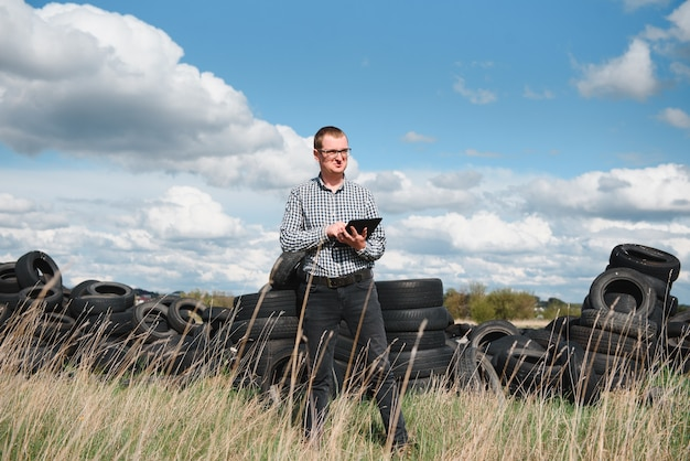 Eco-activist at the landfill of used car tires calculates environmental damage