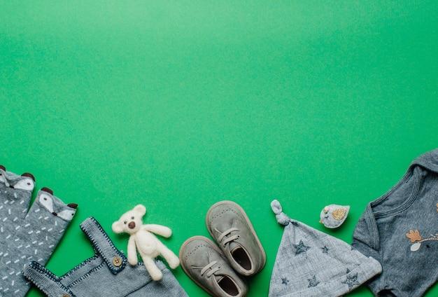 エコベビー服とアクセサリーのコンセプト。テキスト用の空白のある緑の背景に木のおもちゃ、服、靴。上面図、フラットレイ。
