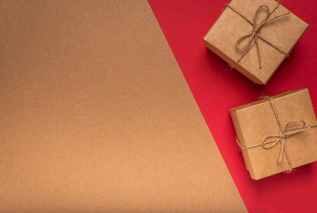 Эко фон текстуры картона ремесла с двумя подарочными коробками на красном с копией пространства на 14 февраля.