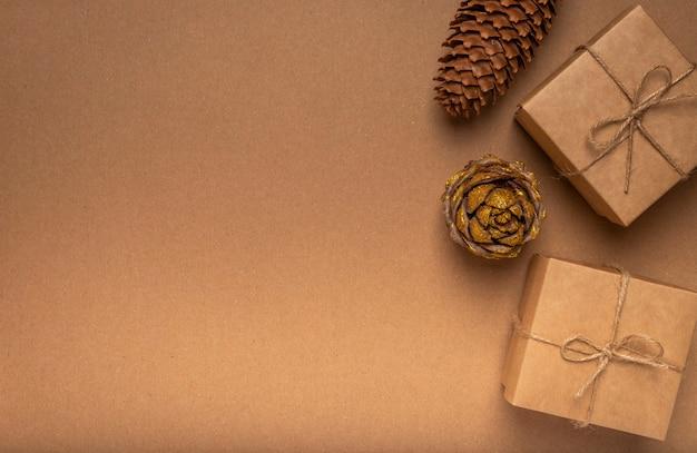 Эко фон текстуры картона ремесла с двумя подарочными коробками, шишкой и джутовой нитью.
