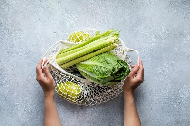 Эко-сумка и зеленые овощи. здоровая пища фон. плоская планировка. устойчивый образ жизни.