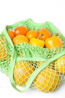 Эко сумка из ткани с овощами и желтыми фруктами на белом фоне.