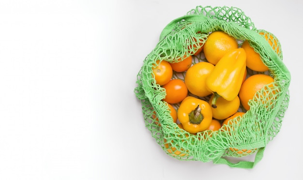 Эко сумка зеленого цвета с овощами на белом фоне.