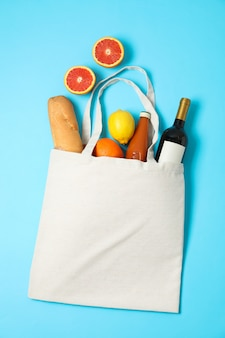 Eco bag with bottle of wine, juice, fruits and baguette on color background