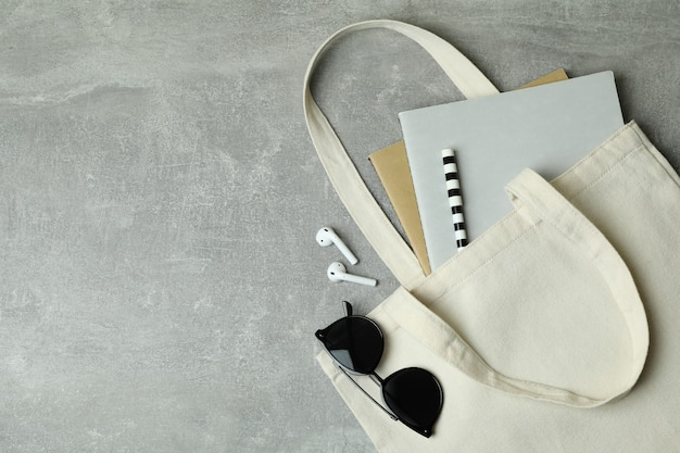 Eco bag with copybooks, headphones and sunglasses on gray background