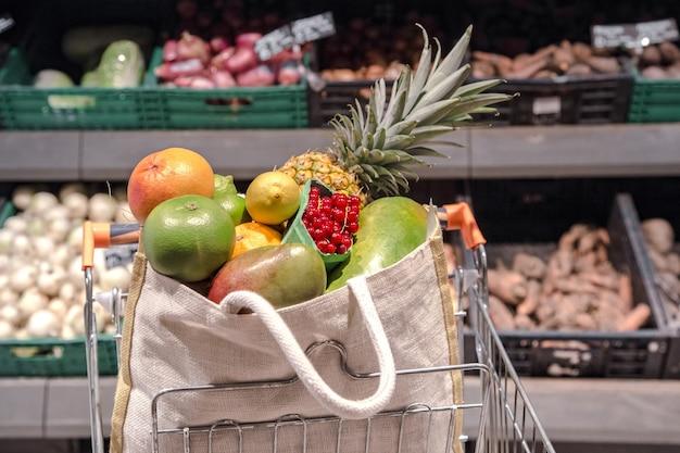 ショッピングカートにさまざまな果物や野菜が入ったエコバッグ