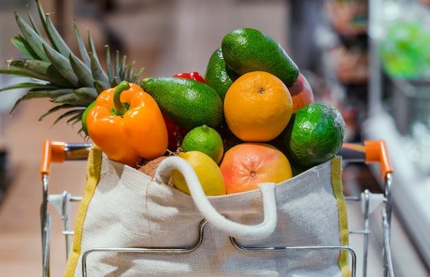 さまざまな果物や野菜が入ったエコバッグ。スーパーマーケットでの買い物。