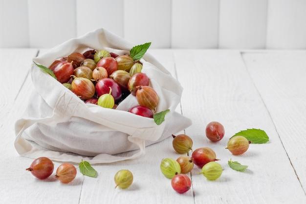 白い木製のテーブル、テキスト用のスペースに新鮮な熟したグーズベリーとエコバッグ