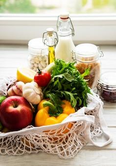 과일과 채소가 들어있는 에코 백, 콩, 파스타, 우유, 기름이 들어있는 유리 병