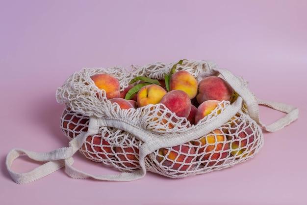 분홍색 배경에 과일이 있는 에코백. 신선한 복숭아가 든 내츄럴 쇼핑백.