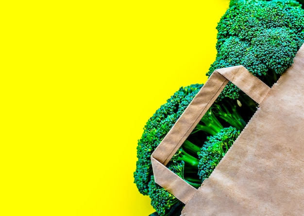 Eco bag with groceries on a yellow background juicy greens and broccoli