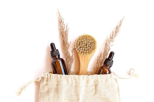 自家製の天然オーガニック化粧品と木製の顔のマッサージブラシが付いたエコバッグ。スキンケア環境にやさしいアクセサリー。有機、ゼロウェイスト化粧品のコンセプト。