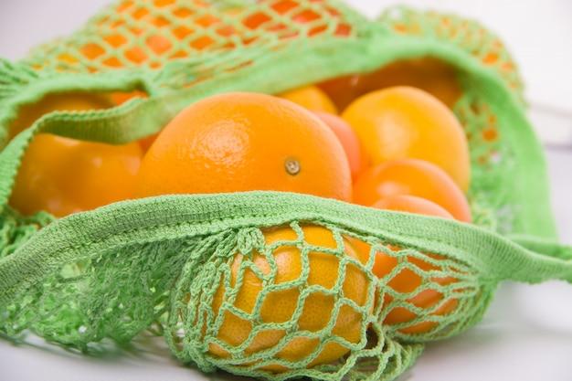 Эко сумка с апельсинами на белом фоне