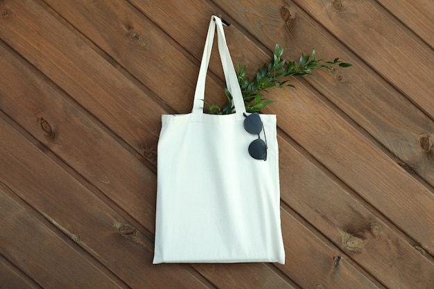 Eco bag with twig and sunglasses on wooden background