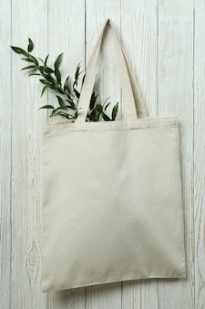 Eco bag with twig on white wooden background