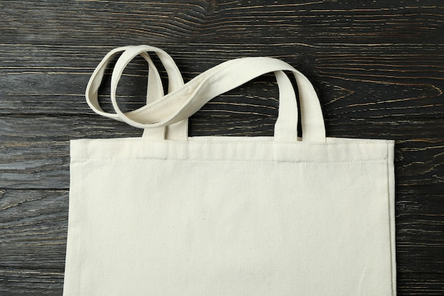 Eco bag on wooden background, space for text