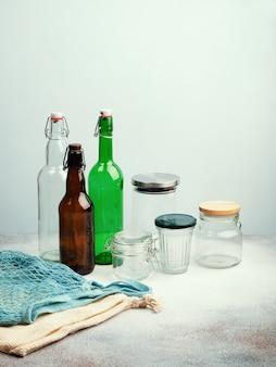 Эко сумки, многоразовые стеклянные бутылки и банки на столе