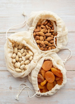 Eco bags with pistachios, almonds and dried apricots on a wooden surface