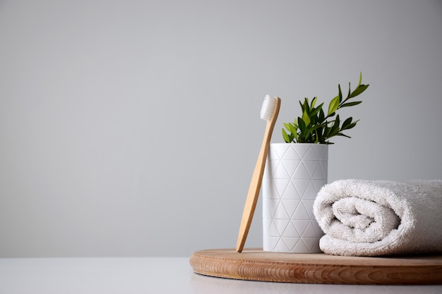 Eco bamboo tooth brush near white holder and white rolled towel on wooden round board