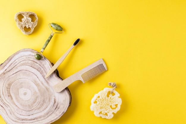 エコビューティーコンセプト。翡翠のフェイスローラー、ヘチマのスポンジ、歯ブラシ、木製の櫛、黄色い表面に木のスライス。エコロジー素材を使った美容アイテム一式。お風呂の無駄ゼロ。コピースペース、フラットレイ