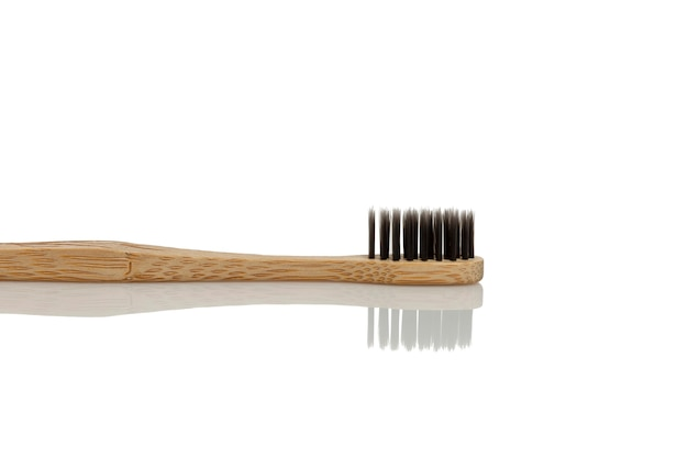 Eco charcoal toothbrush with wooden handle. caring for nature. isolated on white background. space for text.