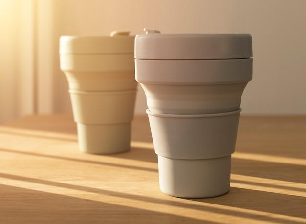 窓からの美しい日光と木製のテーブルの上のエココーヒーカップ。持続可能なライフスタイルのオブジェクト。
