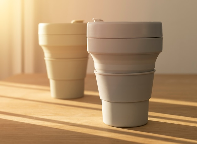 Eco coffe cups on wooden table with beautiful daylight from window. objects of sustainable lifestyle.