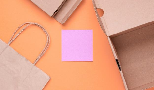 Эко-концепция. картонные коробки, бумажный пакет, памятный лист на желтом