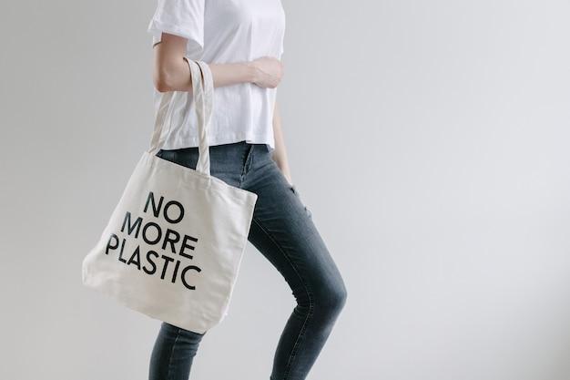 白いテキスタイルエコバッグを持っている女性のエココンセプト