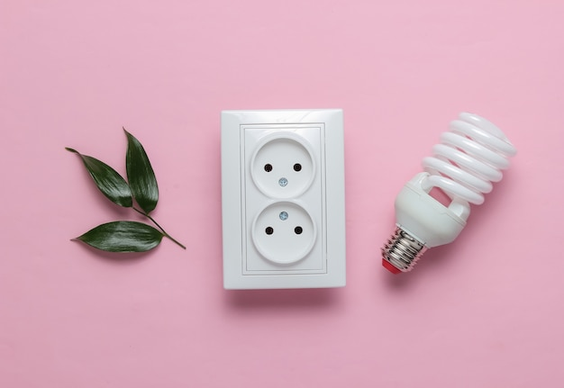 에코 개념 전력 에너지 경제 행성을 저장하십시오 이중 전원 소켓 녹색은 분홍색 파스텔 배경에 나선형 전구를 떠납니다.