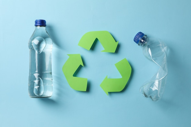 Eco concept with recycling symbol and bottles on blue