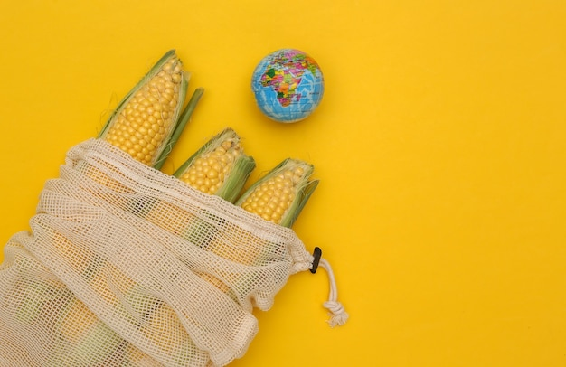 Eco cotton bag with corn swings and globe on yellow background. save planet.