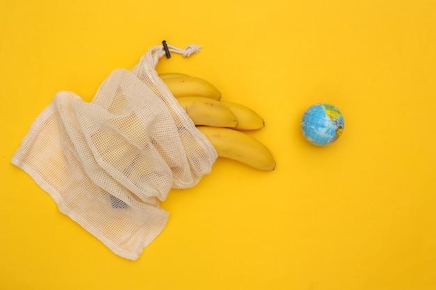 노란색 배경에 잘 익은 바나나와 글로브가 있는 에코 면 가방. 행성을 저장합니다.