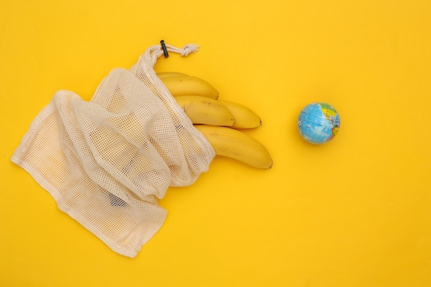 Eco cotton bag with ripe bananas and globe on yellow background. save planet.