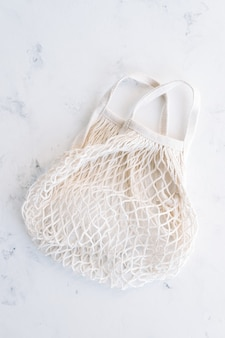 Eco cotton and net shopping bag on white background.
