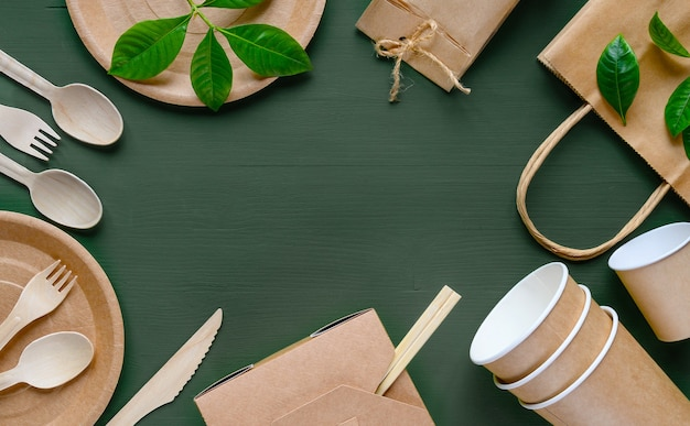Eco craft paper disposable tableware on a green wooden table. wooden spoons, fork, knive, with paper cups, plates, box, bamboo chopstic.
