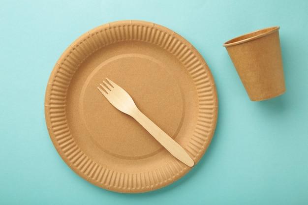 Бумажная посуда eco craft. бумажные стаканчики, посуда, сумка, контейнеры быстрого питания и деревянные столовые приборы на синем фоне. нулевые отходы. концепция утилизации. копировать пространство