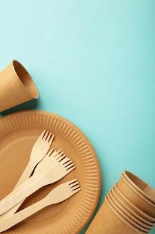 Бумажная посуда eco craft. бумажные стаканчики, посуда, сумки, контейнеры быстрого питания и деревянные столовые приборы на синем фоне. нулевые отходы. концепция утилизации. вертикальное фото