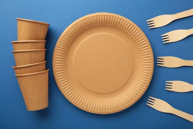 Бумажная посуда eco craft. бумажные стаканчики, посуда, сумки, контейнеры быстрого питания и деревянные столовые приборы на синем фоне. нулевые отходы. концепция утилизации. копировать пространство