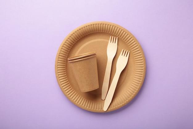 Бумажная посуда eco craft. бумажные стаканчики, посуда, сумки, контейнеры быстрого питания и деревянные столовые приборы на фиолетовом фоне. нулевые отходы. концепция утилизации. копировать пространство