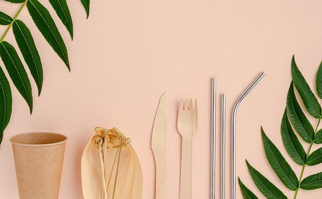 Эко столовые приборы и металлические соломинки для питья на розовом фоне