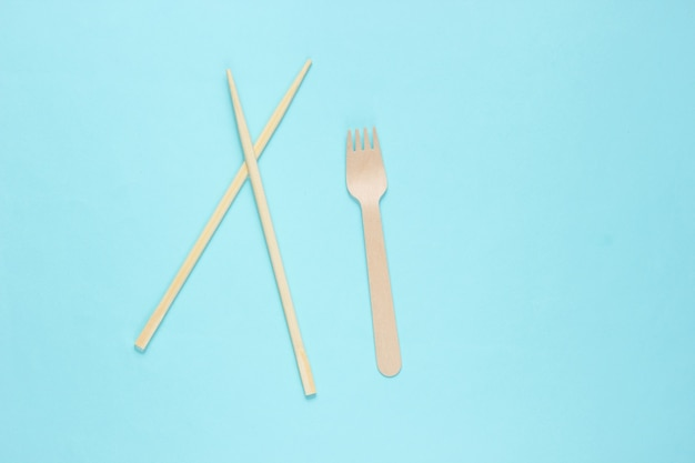 Eco cutlery. chinese chopsticks, wooden fork on blue background.