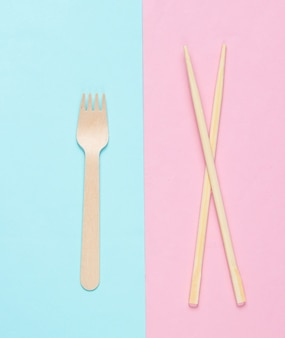 Eco cutlery. chinese chopsticks, wooden fork on blue pink pastel background.