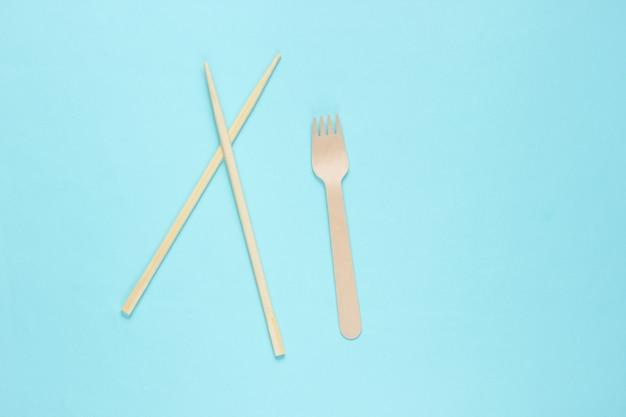 Эко столовые приборы. китайские палочки для еды, деревянная вилка на синем фоне.