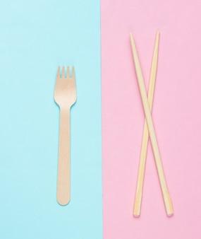 Эко столовые приборы. китайские палочки для еды, деревянная вилка на синем розовом пастельном фоне.