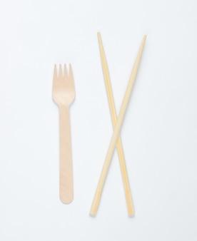 Эко столовые приборы. китайские палочки для еды, деревянная вилка на белом фоне.