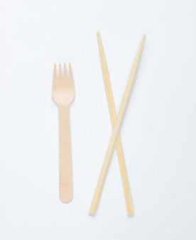 Eco cutlery. chinese chopsticks, wooden fork on white background.