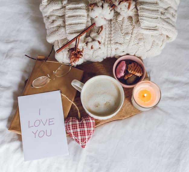 Эко-декор для дома. домашний уютный декор. кружка капучино, печенье, свеча на кровати. зимнее утро. каникулы.