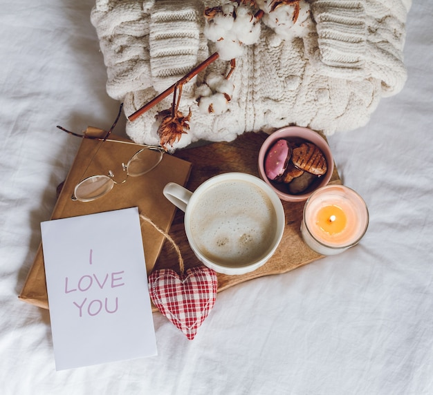Eco decor for the home. home cozy decor. a mug of cappuccino, cookies, a candle on the bed. winter morning. holidays.
